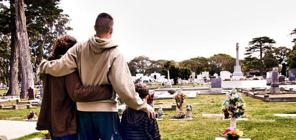 Grieving Family Visiting Cemetery Stock Photo