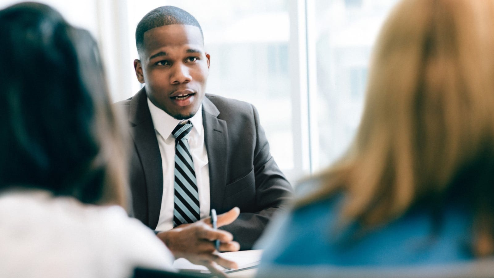 Attorney Consulting Two Clients During A Private Meeting Stock Photo