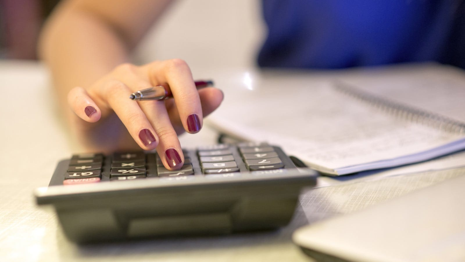 Woman Using A Calculator At Her Desk Stock Photo