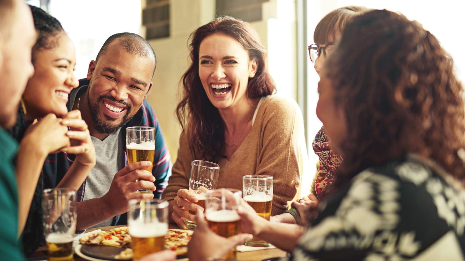 Group Of Friends Eating At A Pub Together Stock Photo