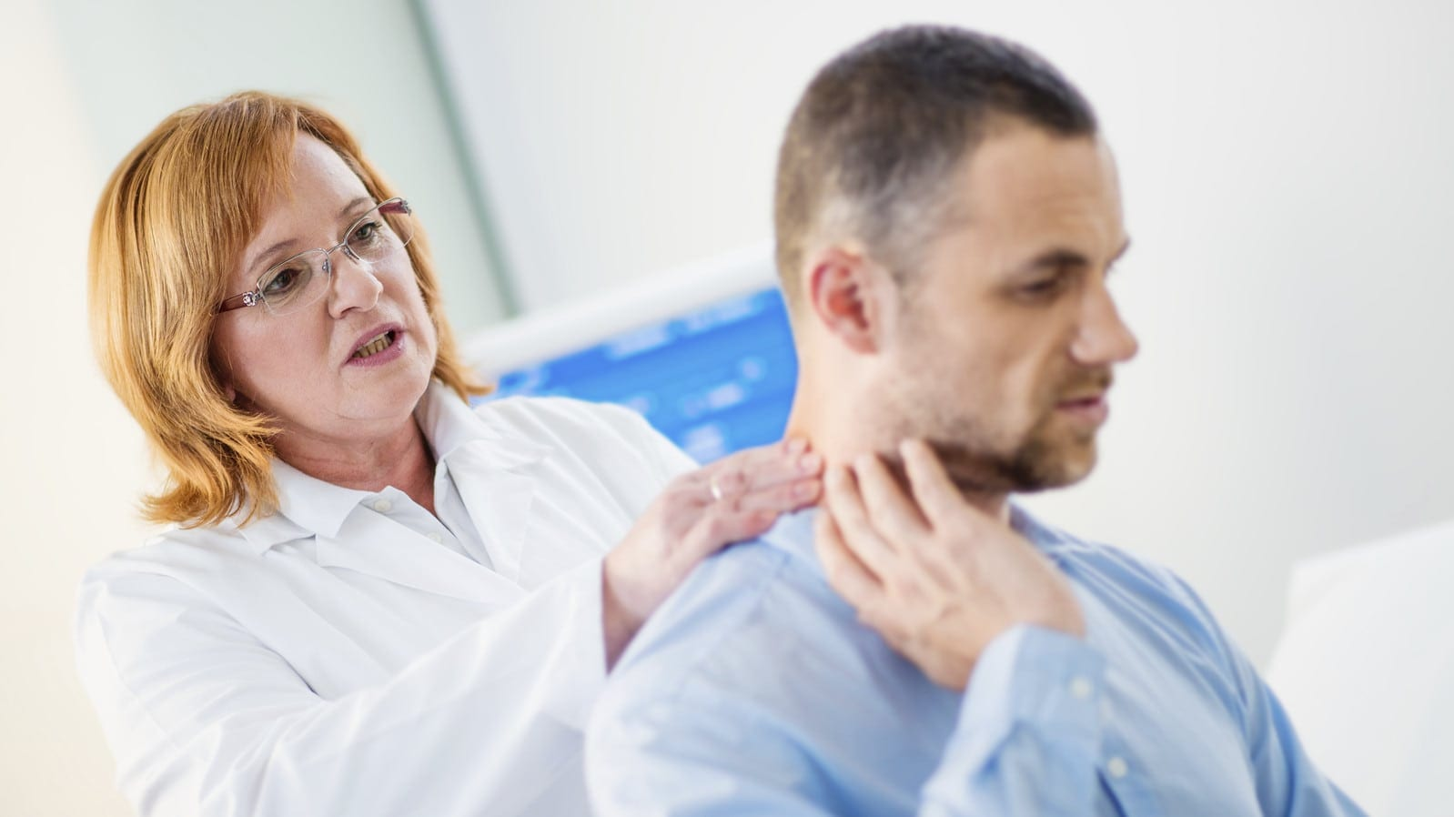 Female Doctor Examining Male Patient's Neck Injury