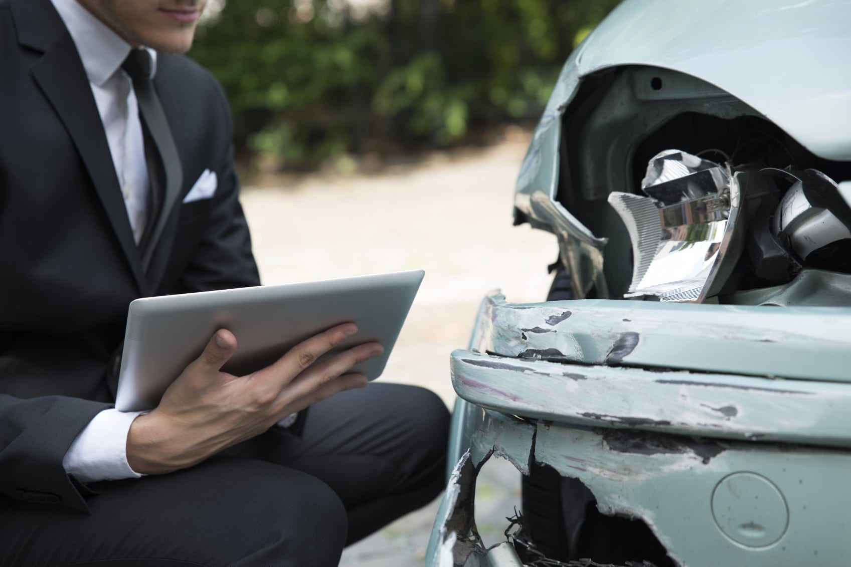 Insurance Agent Examining Car After Accident Stock Photo