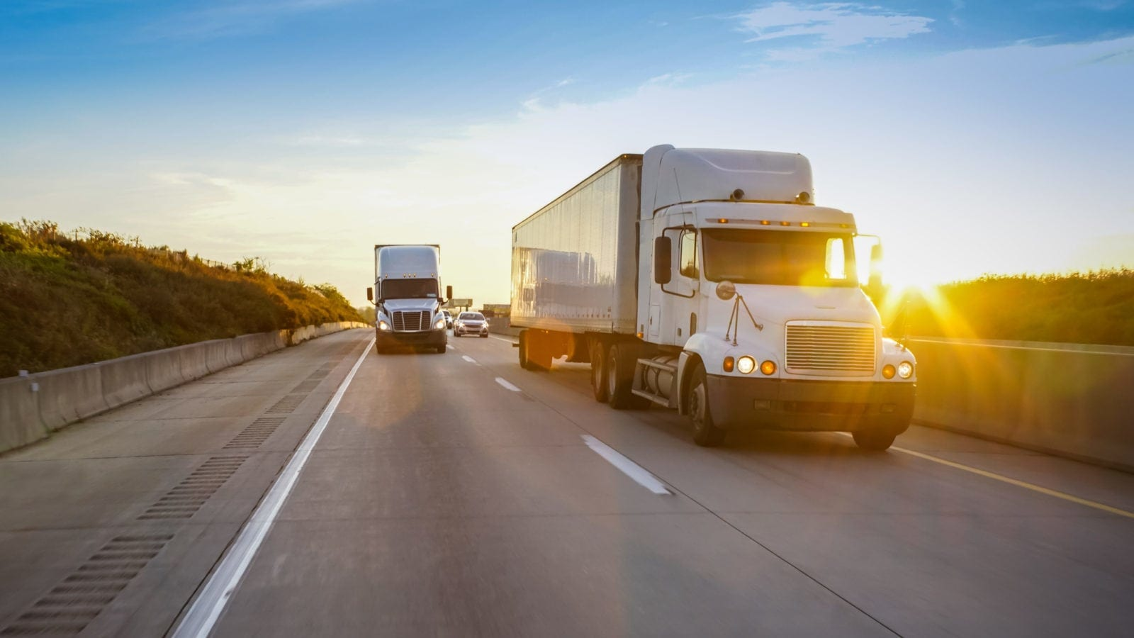 Two Large 18-wheeler Trucks Driving On The Interstate Stock Photo