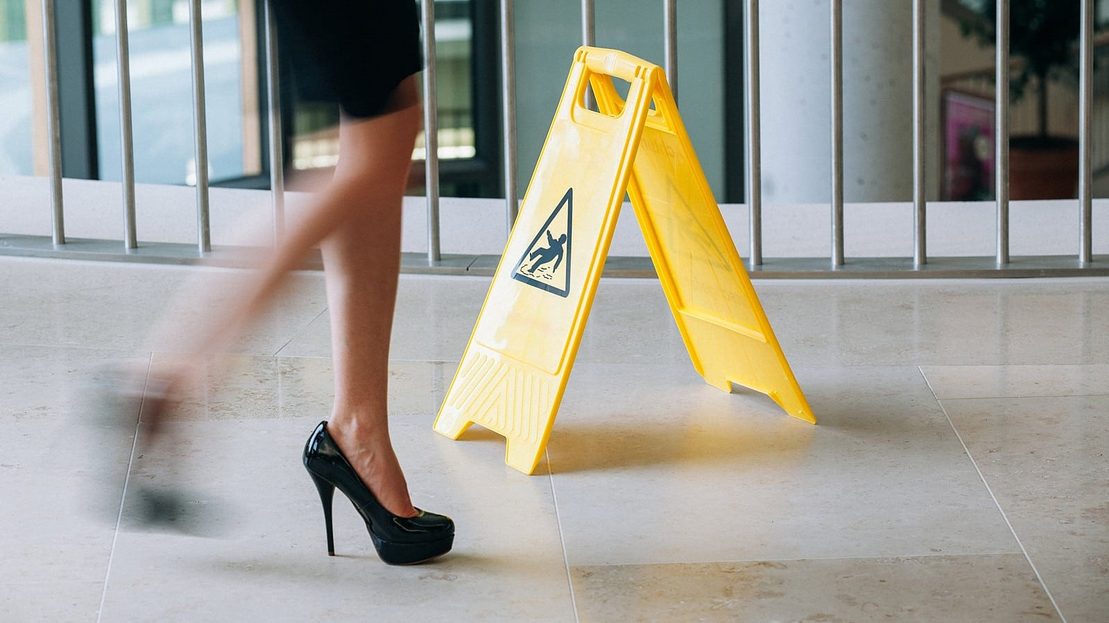 Woman In High Heels Walking Past Caution Slippery Sign