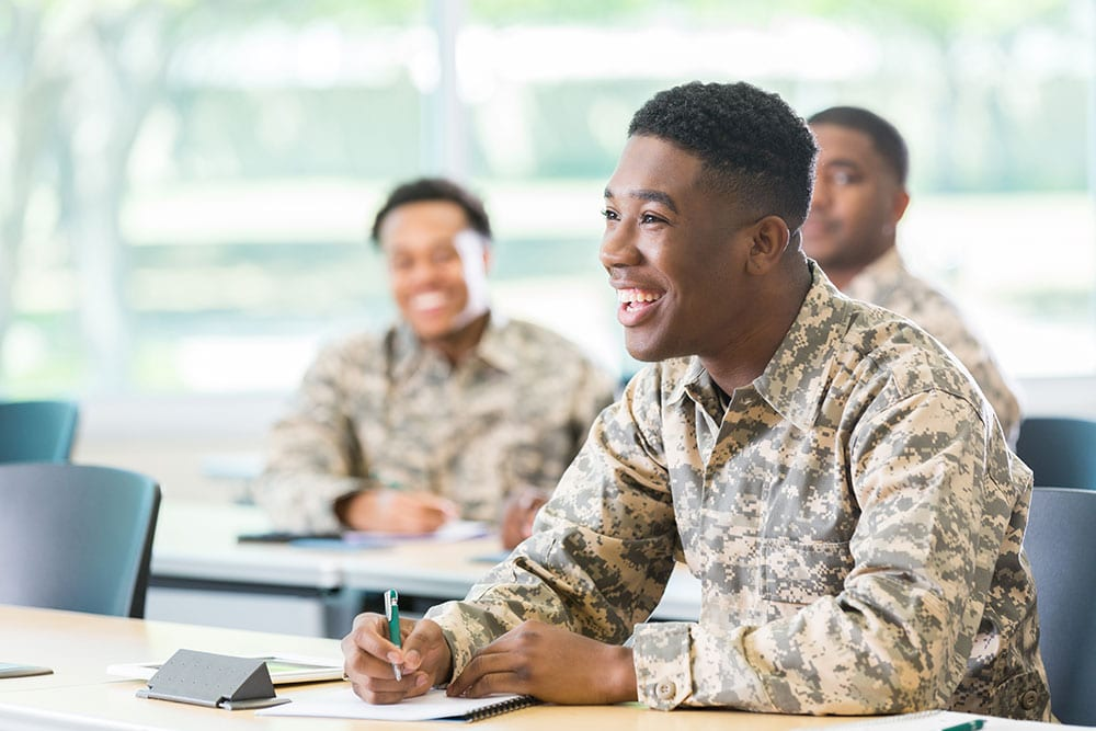 Smiling Soldier Taking Notes In A Classroom