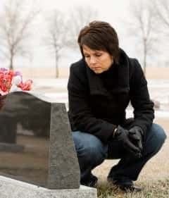 Grieving Woman Visiting A Grave Stock Photo