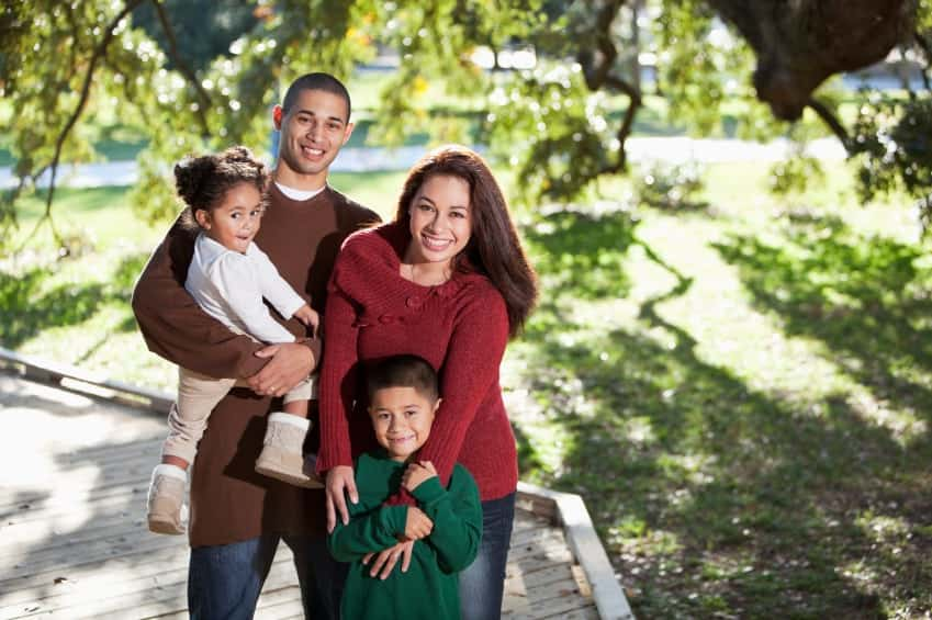 Young Smiling Hispanic Family At The Park Stock Photo