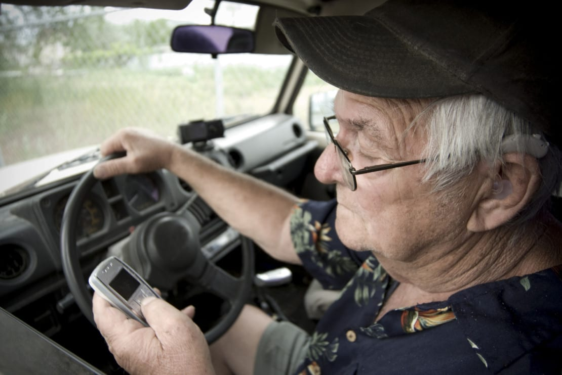 Elderly Man Texting While Driving Stock Photo