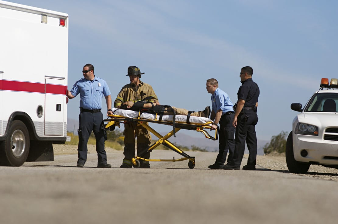 Injured Man On Stretcher Being Loaded Into An Ambulance