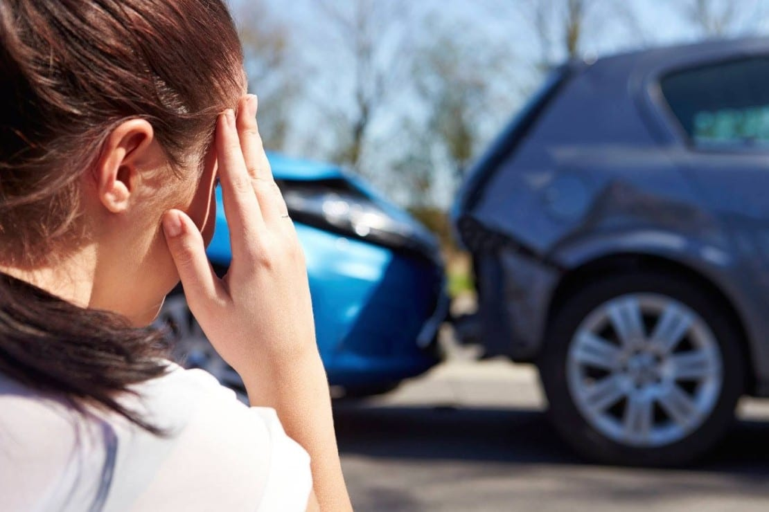 Female Driver Examining Rear End Car Accident Stock Photo