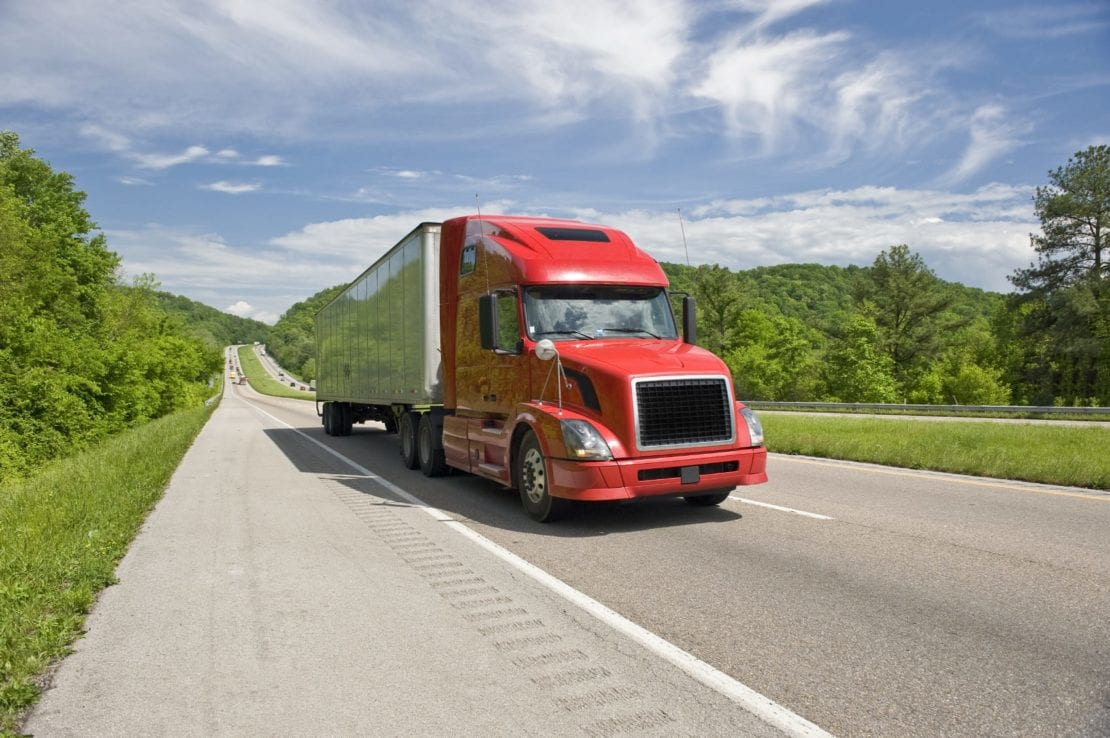 Red 18-wheeler Truck Driving On A Rural Highway
