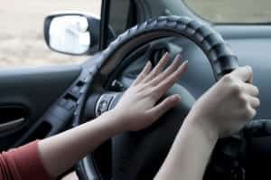 Young Woman Honking Her Vehicle's Horn In Traffic
