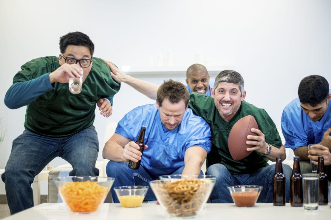 Group Of Guy Friends Drinking And Watching Football