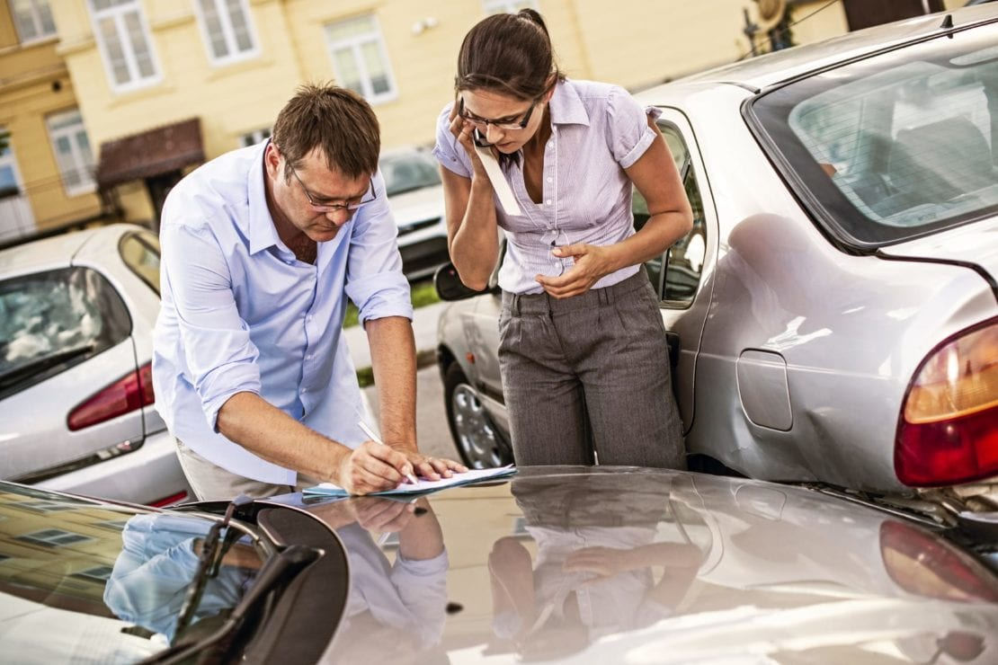 Man And Woman Exchanging Insurance Information After Accident