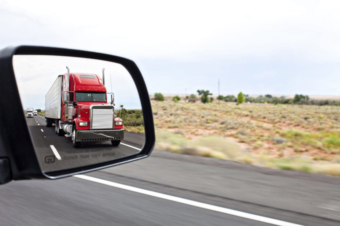 Large Semi-truck In Rear View Mirror Stock Photo