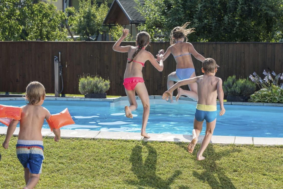 Young Children Jumping Into A Swimming Pool Stock Photo
