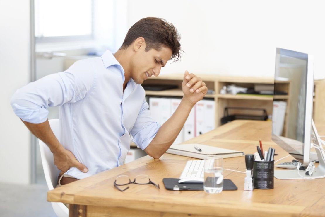 Young Man Experiencing Lower Back Pain At Desk Stock Photo
