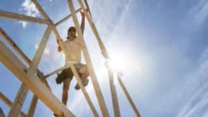 Man Climbing Foundation Of House Stock Photo