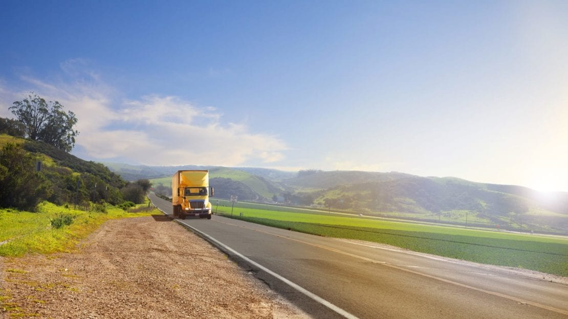 Yellow Semi-truck Driving On The Highway Stock Photo
