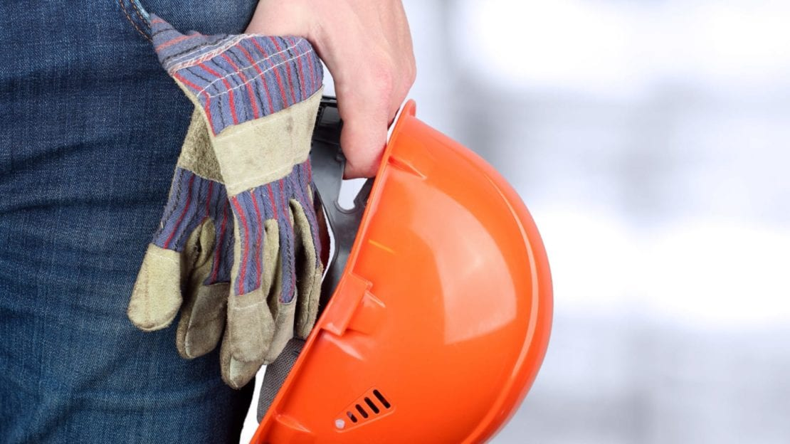Blue Collar Worker Holding Hard Hat And Work Gloves Stock Photo