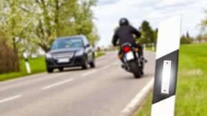 Motorcyclist Passing A Car On A Rural Road Stock Photo
