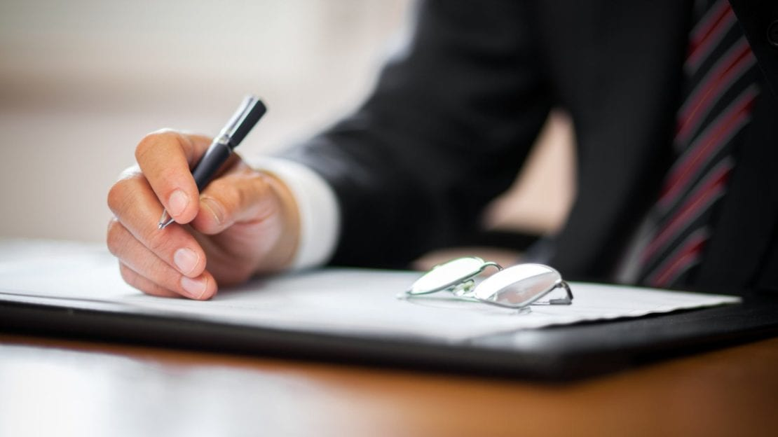Insurance Adjuster Signing A Document Stock Photo