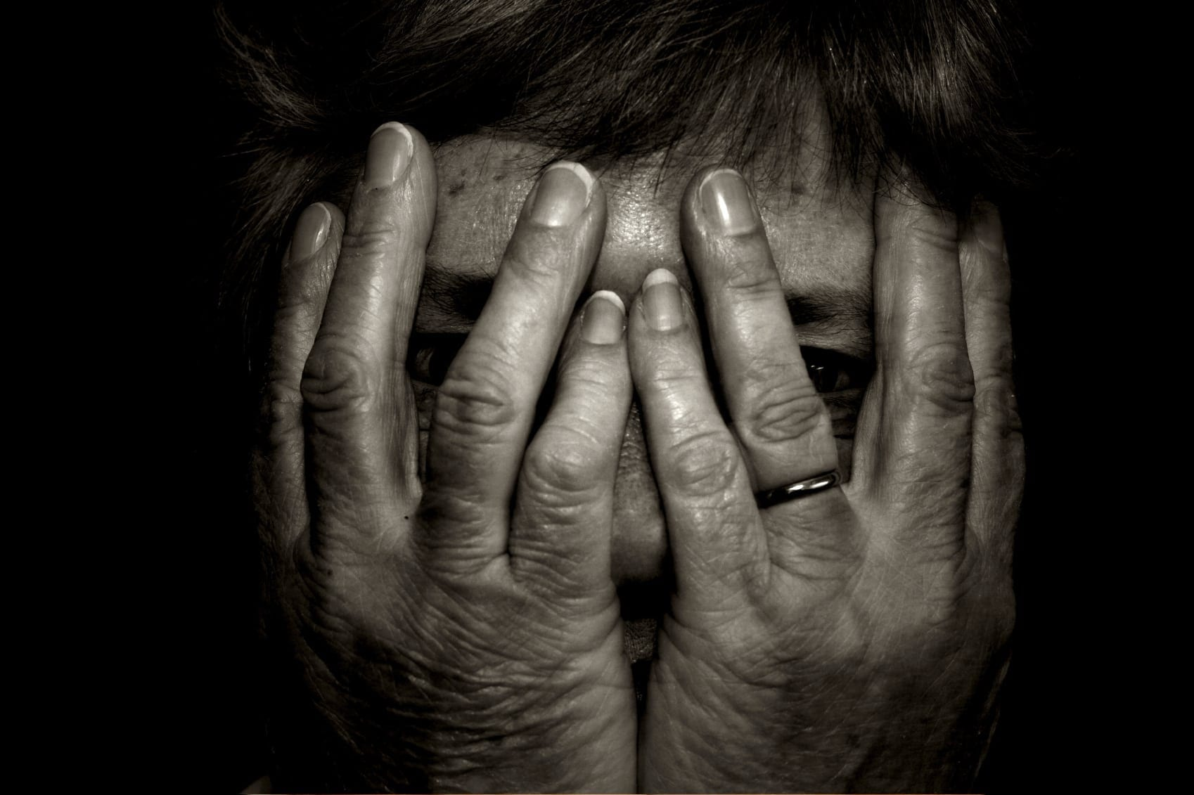 Elderly Woman With Hands Over Her Face Stock Photo