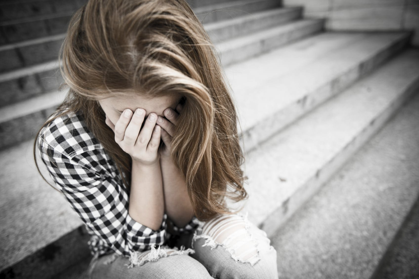 Young Woman Crying On Steps Stock Photo