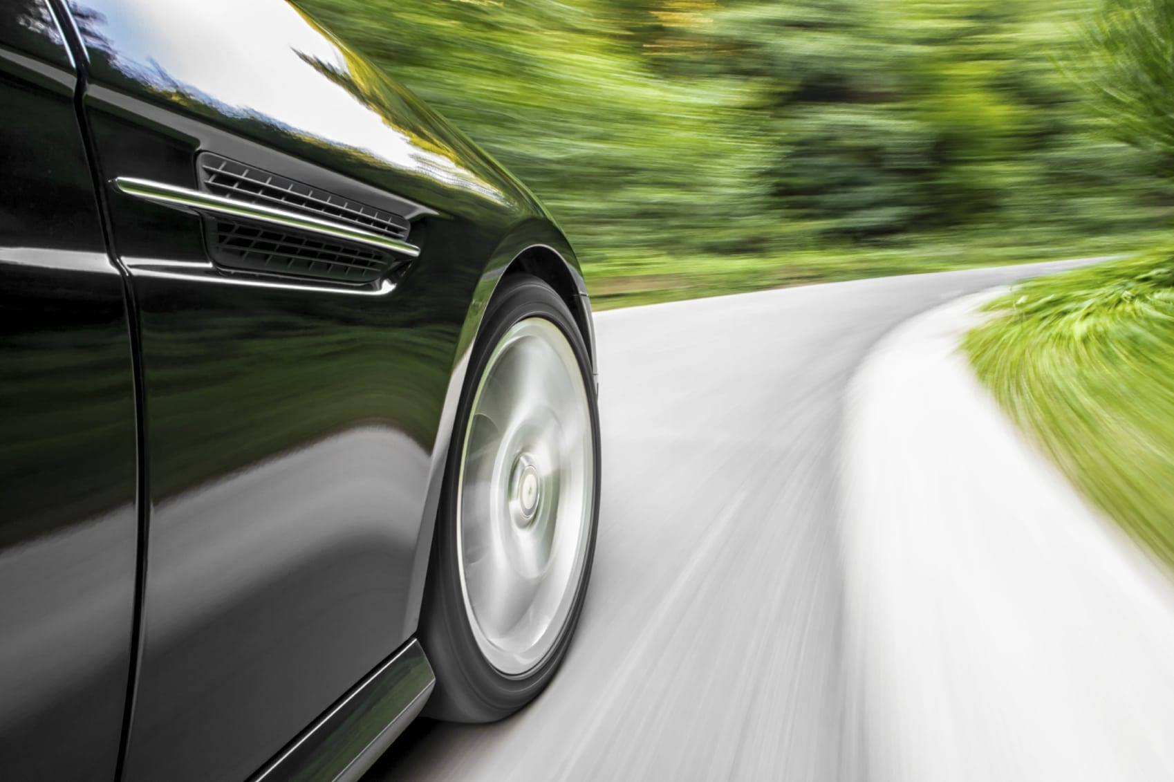 Black Car Driving On A Windy Rural Road Stock Photo