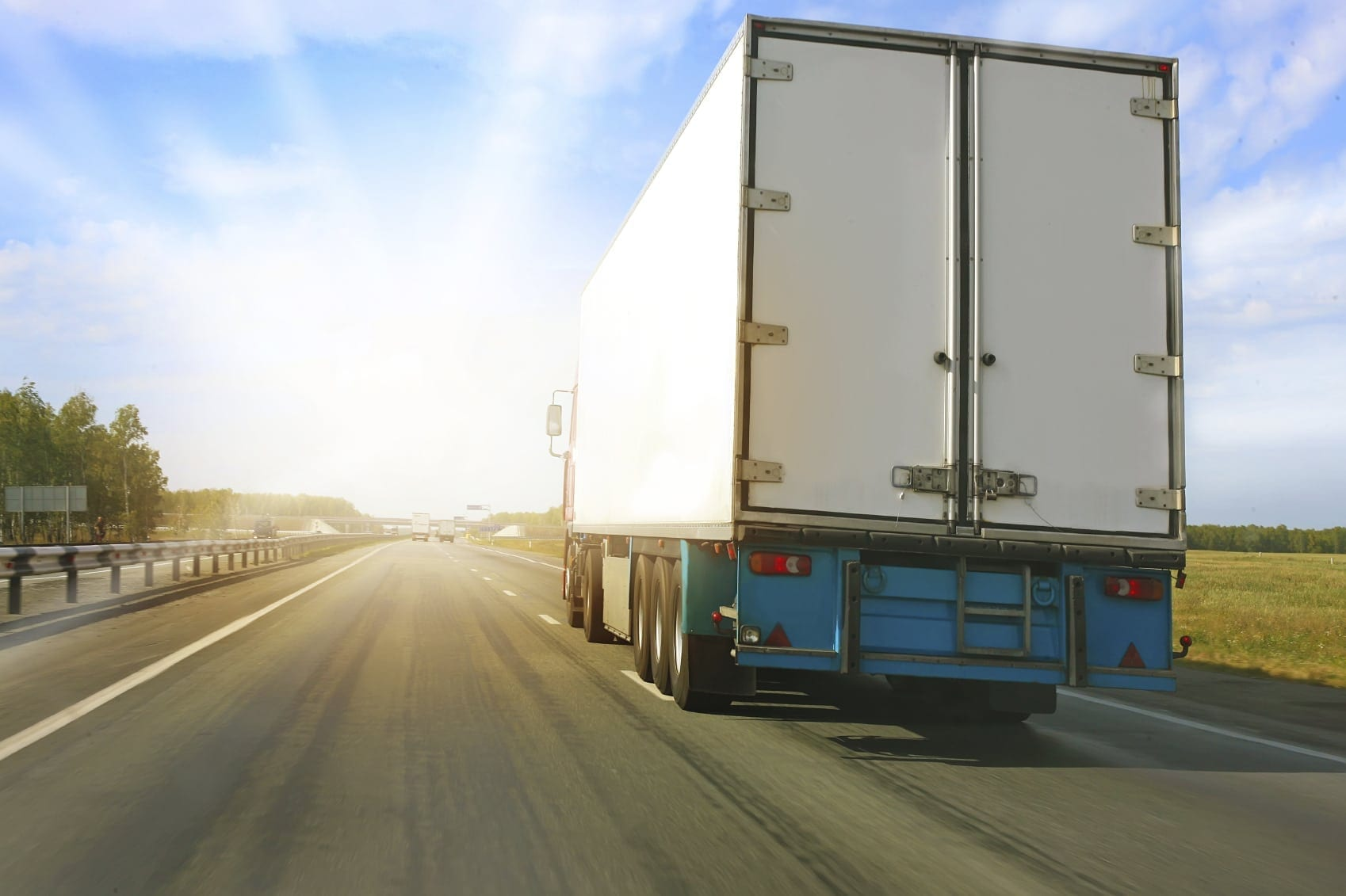White 18-wheeler Truck Driving On The Interstate Stock Photo