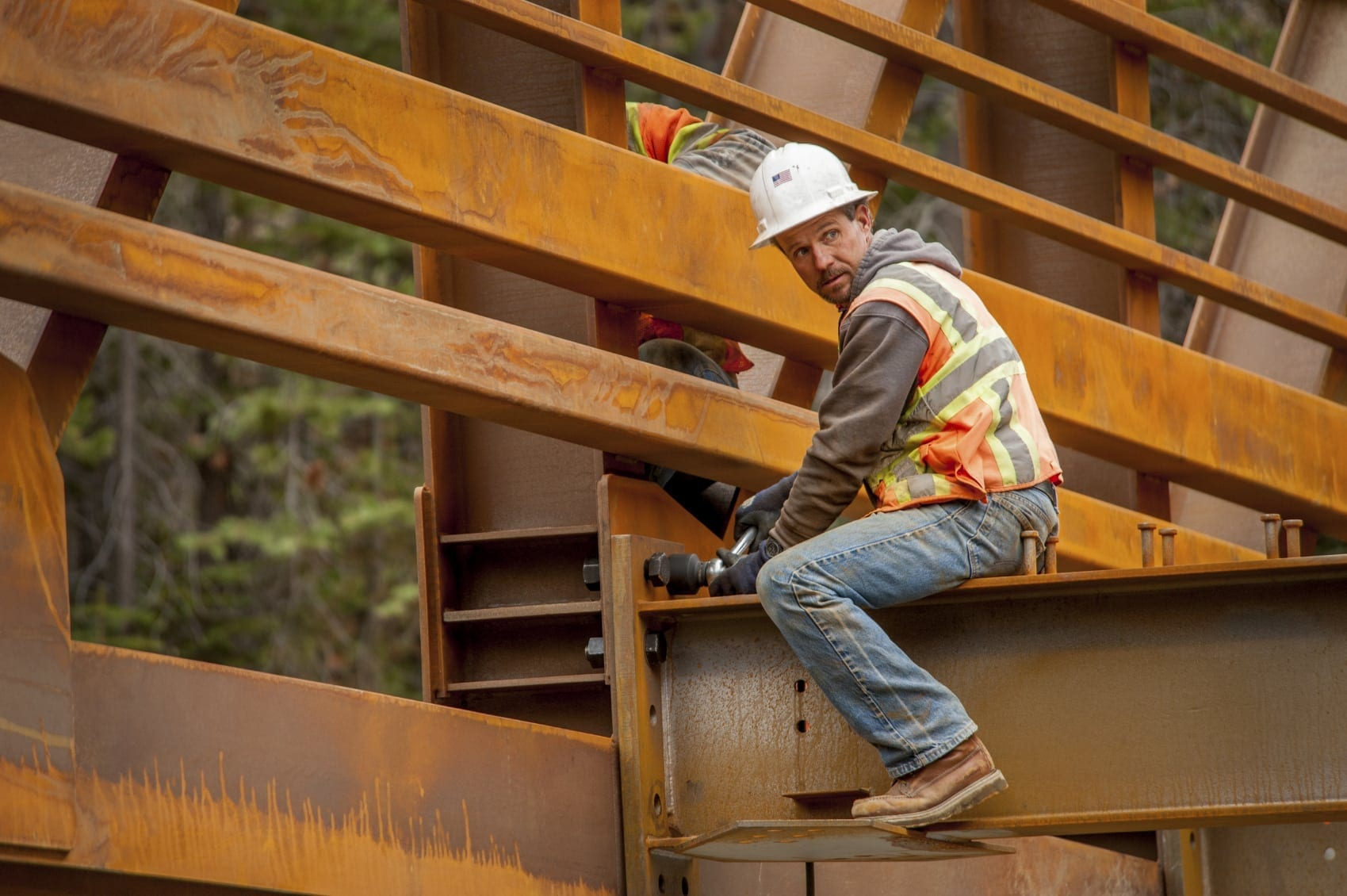 Construction Worker Sitting On The Structure Of A Bridge Stock Photo