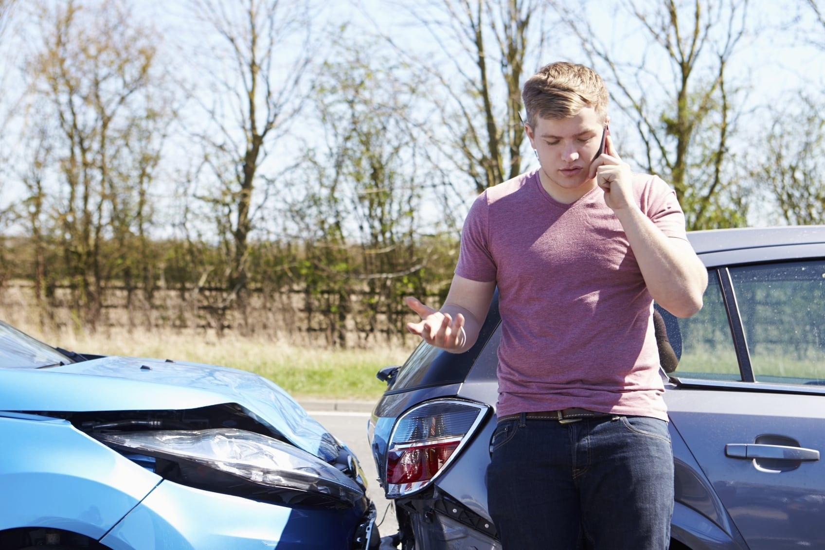 Young Man Reporting Car Accident To Police Stock Photo