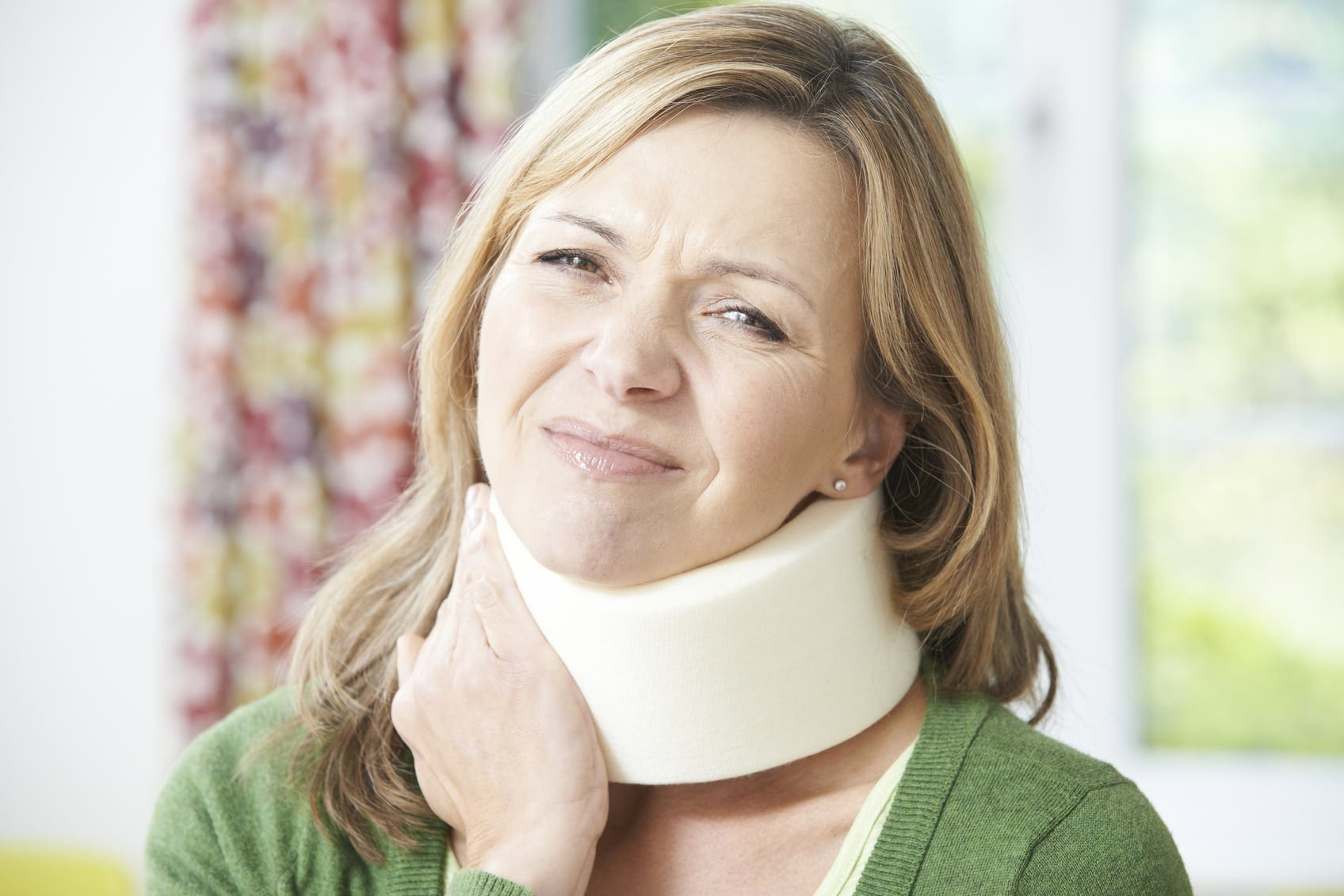 Woman Experiencing Pain While Wearing Neck Brace