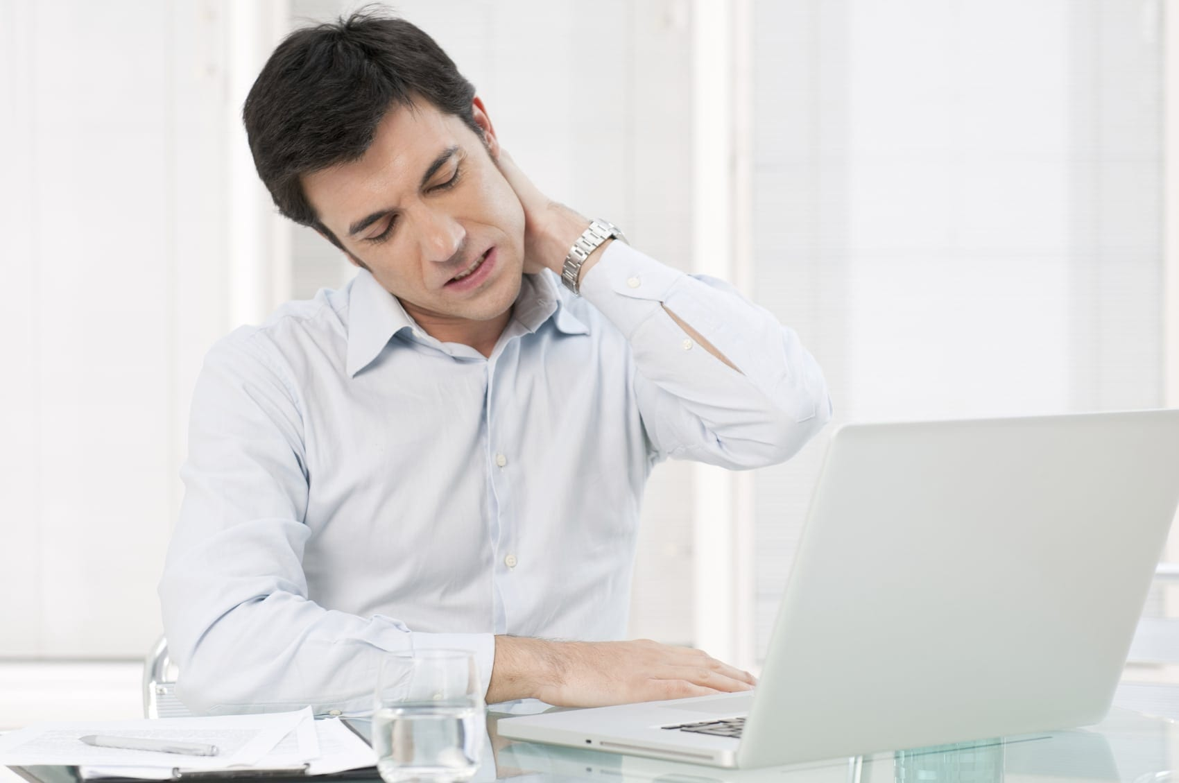 Man Experiencing Neck Pain While Working On Laptop Computer