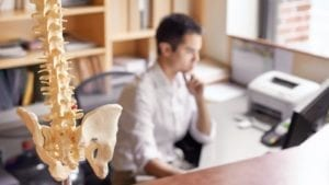 Male Chiropractor Working In His Office Stock Photo