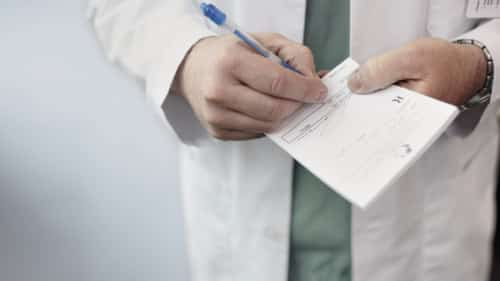 Doctor Writing A Prescription For A Patient Stock Photo