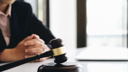 Lawyer Sitting Next To A Gavel Stock Photo