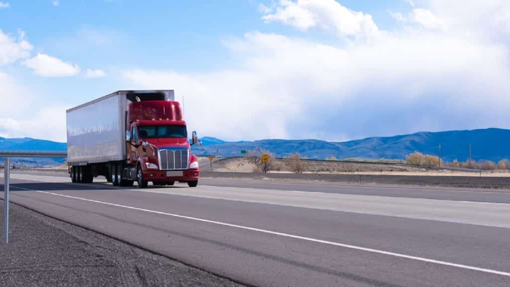 Red 18-wheeler Driving On The Interstate Stock Photo