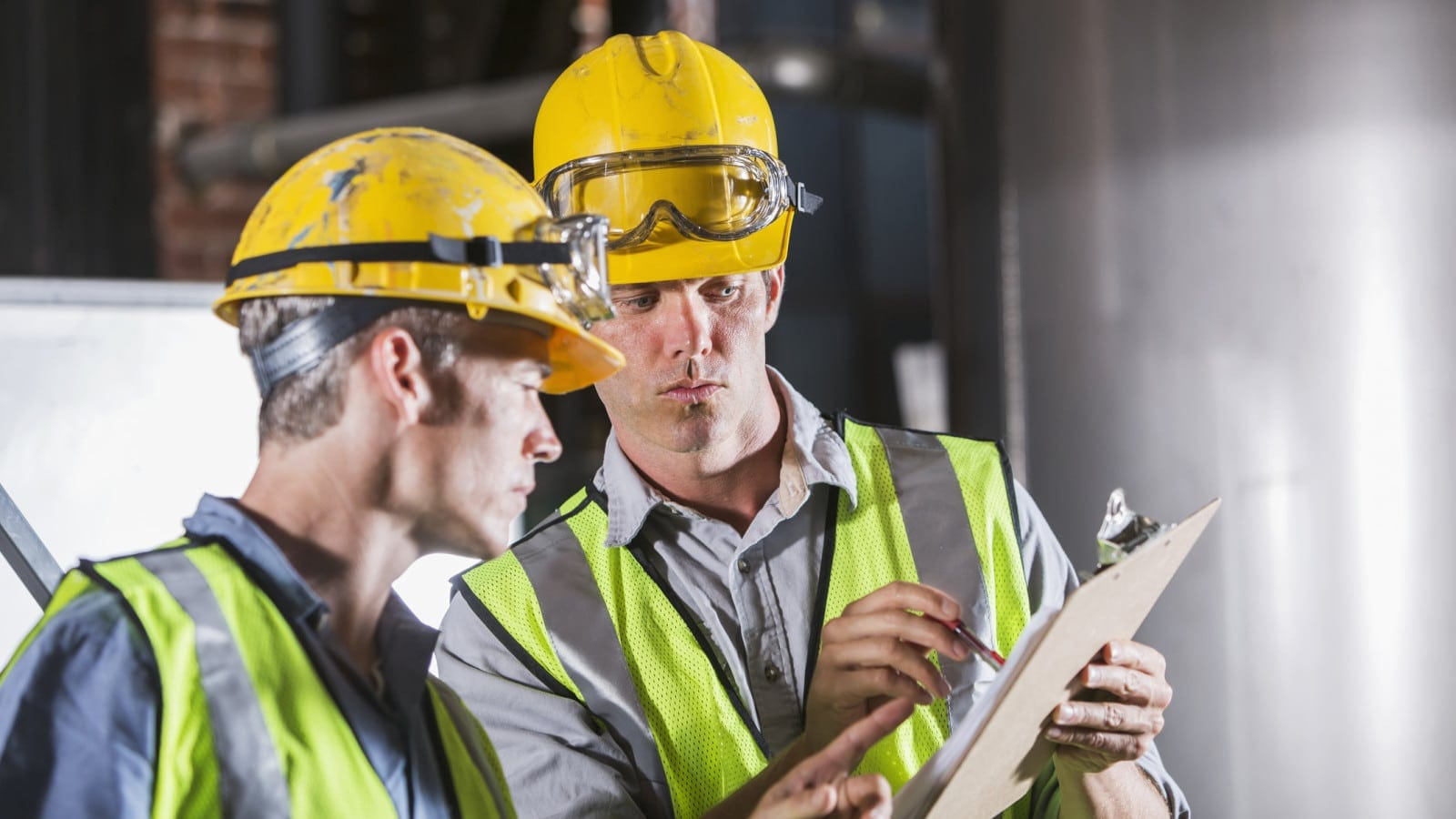 Two men working together, wearing hardhats, safety glasses and vests.