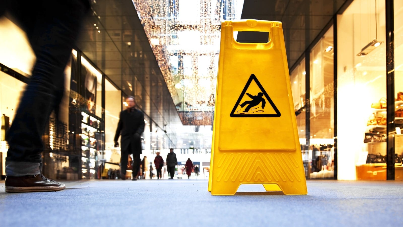 Danger sign in a shopping mall, in the background are motion blurred people.