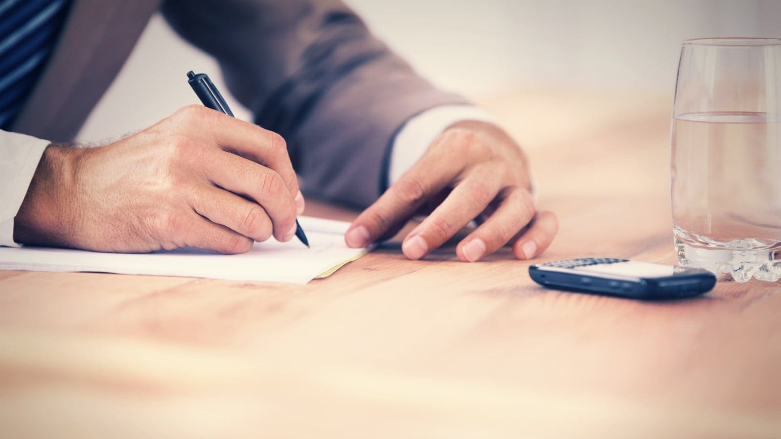 A lawyer taking notes during a meeting.