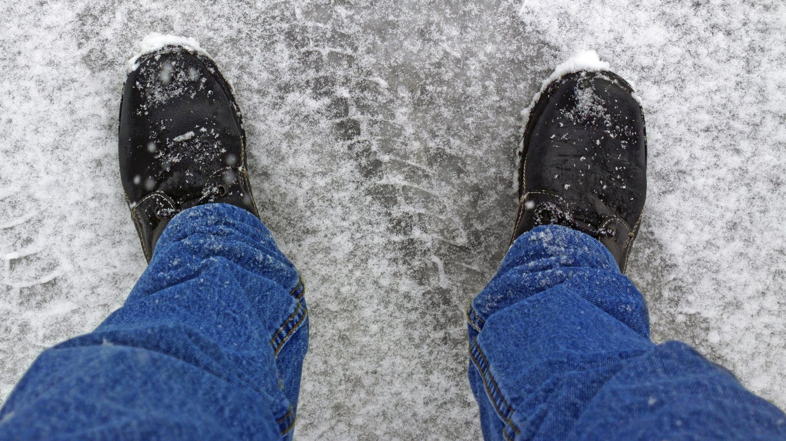 A man's shoes on a slippery icy road.