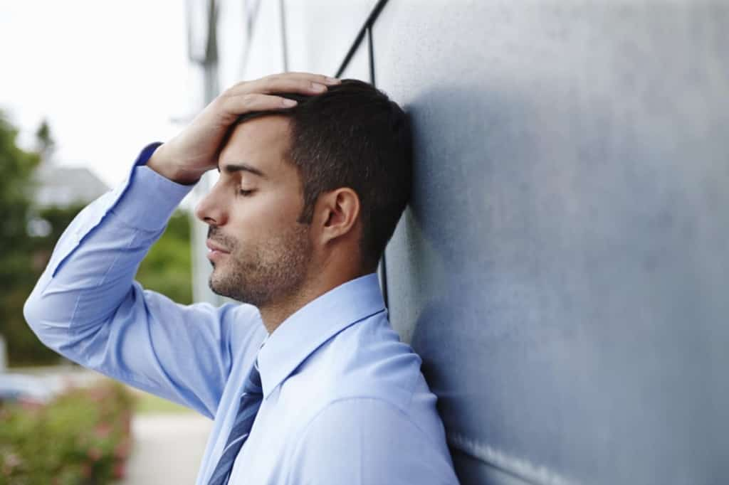 A stressed young businessman standing outdoors with his head in his hands