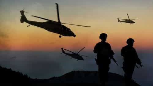 Soldiers Watching Helicopters Fly At Dusk Stock Photo