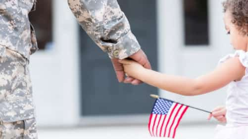 Soldier Holding Hands With Young Daughter Stock Photo