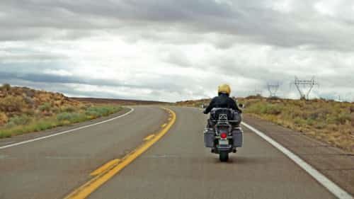 Motorcyclist Riding Motorcycle On A Rural Road Stock Photo