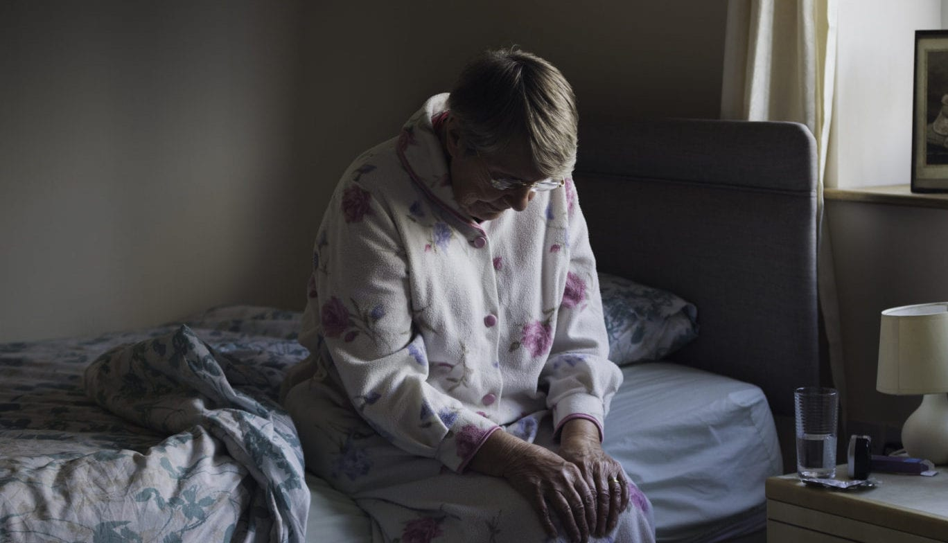 Elderly Woman Sitting On Her Bed Stock Photo
