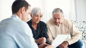 Elderly Couple Meeting With An Attorney In Their Home