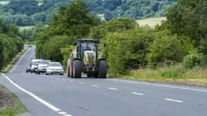 Tractor Driving On A Rural Road Stock Photo