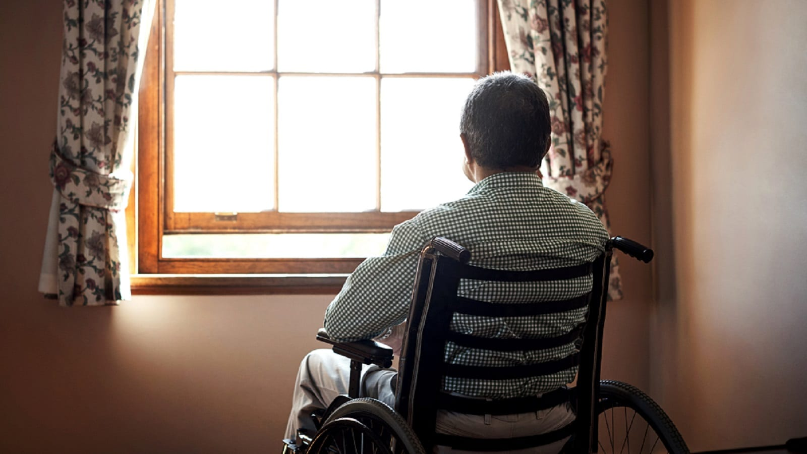 Senior Man In Wheelchair Staring Out The Window Stock Photo